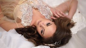 Schöne Braut wird durch Brautkleider, liegt umgeben, ohne, große schöne Augen sich zu bewegen stock footage
