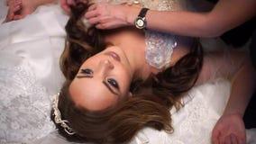 Schöne Braut wird durch Brautkleider, Make-upkünstler korrigiert Haar umgeben stock footage
