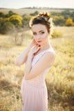 Schöne Brautjungfer in Rosenquarz farbigem Kleid Stockfotos