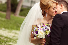 Schöne Brautpaare, die Spaß im Park auf ihrem Hochzeitstagblumenblumenstrauß haben Stockbild