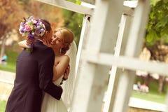 Schöne Brautpaare, die Spaß im Park auf ihrem Hochzeitstagblumenblumenstrauß haben Lizenzfreies Stockbild