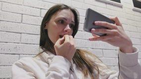 Schöne brunette Frau aufpassendes überraschendes seria einer Serie in den Kopfhörern am Handy auf einer weißen Wand des Ziegelste stock video footage