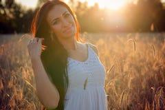 Schöne brunette Frau des Porträts auf Sonnenunterganghintergrund im Sommer stockfoto