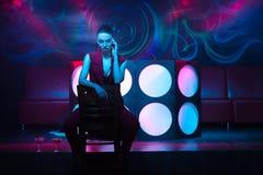 Schöne brunette Frau, die auf dem Tanzboden auf Stuhl sitzt stockbilder