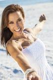 Schöne Brunette-Frau, die auf einem Strand lacht lizenzfreies stockbild