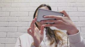 Schöne brunette Frau, die eine Serie in den Kopfhörern am Handy auf einem weißen Wandhintergrund des Ziegelsteines aufpasst stock video footage
