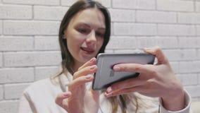 Schöne brunette Frau, die eine Serie in den Kopfhörern am Handy auf einem weißen Wandhintergrund des Ziegelsteines aufpasst stock video