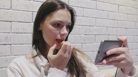 Schöne brunette Frau, die schreckliches seria einer Serie in den Kopfhörern am Handy auf einer weißen Wand des Ziegelsteines aufp stock video