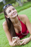 Schöne Brunette-Frau, die zum MP3-Player hört lizenzfreie stockfotografie