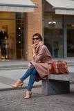 Schöne brunette junge Frau im netten braunen beige Mantel, in den Jeans und in der Sonnenbrille Schuhe der Frauen auf den hohen A stockfotos