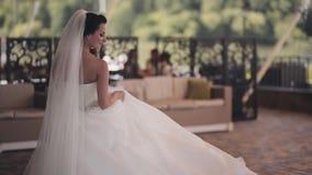 Schöne Brunettebraut, die sich herum in weißes Kleid dreht Glückliche Frau bei der Hochzeitstagaufstellung, die Feier genießend stock footage