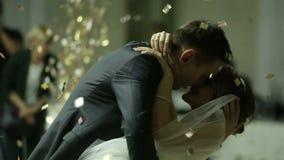 Schöne Brunettebraut und hübscher Bräutigam, die zuerst Tanz am Hochzeitsfest eingehüllt durch Konfettis tanzt Sehr Angebot stock footage