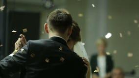 Schöne Brunettebraut und hübscher Bräutigam, die zuerst Tanz am Hochzeitsfest tanzt Konfettis in der Luft Sehr Angebot stock video
