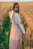 Schöne Brunettedame auf dem Weizengebiet bei Sonnenuntergang stockfotografie