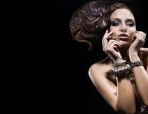 Schöne Brunettedame, die mit erstaunlicher Frisur aufwirft. Stockfotografie