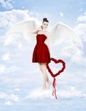 Schöne Brunettefrau als Amor mit dem Herzen gemacht von den Rosen Stockfotografie