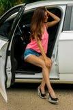 Schöne Brunettefrau auf hohen Absätzen sitzt in einem weißen Auto Lizenzfreie Stockbilder