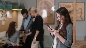 Schöne Brunettefrau benutzt eine Tablette des Bildschirm- im modernen Startbüroteam an dem Arbeitsplatz Stockfoto