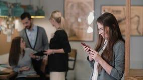 Schöne Brunettefrau benutzt eine Tablette des Bildschirm- im modernen Startbüroteam an dem Arbeitsplatz Lizenzfreies Stockbild