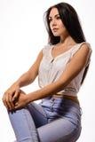 Schöne Brunettefrau in der weißen Spitze und Jeans auf Stuhl lizenzfreies stockfoto