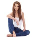 Brunettefrau, die auf dem Boden sitzt. Studiotrieb. Lizenzfreies Stockbild