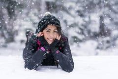Schöne Brunettefrau, die auf dem Schnee, den Winterschnee genießend liegt Lizenzfreie Stockfotos