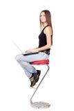 Schöne Brunettefrau, die auf einem Stuhl sitzt und einen Laptop hält Stockfotos