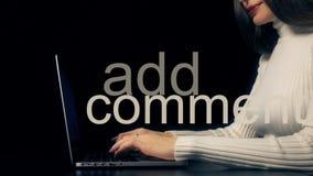Schöne Brunettefrau, die auf ihrem Laptop gegen schwarzen Hintergrund schreibt Addieren Sie Kommentaraufschrift Lizenzfreies Stockfoto
