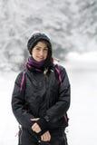 Schöne Brunettefrau, die in den Winterwald, den Winterschnee genießend geht Stockbilder