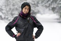 Schöne Brunettefrau, die in den Winterwald, den Winterschnee genießend geht Stockfoto