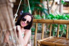 Schöne Brunettefrau, die in der Hängematte im exotischen Luxushotel sich entspannt stockfotografie