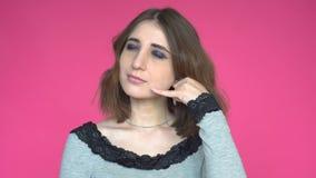 Schöne Brunettefrau, die einen Anruf mich Geste beim Betrachten der Kamera über rosa Hintergrund macht stock video