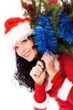 Schöne Brunettefrau, die einen Weihnachtsbaum trägt Lizenzfreie Stockfotos