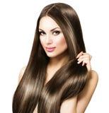 Schöne Brunettefrau, die ihr langes Haar berührt