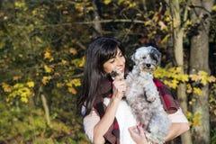 Schöne Brunettefrau, die ihren kleinen netten weißen Hund lächelt und umarmt Lizenzfreie Stockfotos