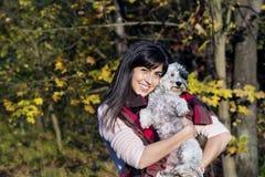 Schöne Brunettefrau, die ihren kleinen netten weißen Hund lächelt und umarmt Stockbild