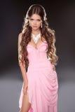 Schöne Brunettefrau, die im rosa herrlichen Kleid lokalisiert aufwirft Stockfotos