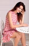 Schöne Brunettefrau, die nahe einer Tabelle sitzt Stockbild