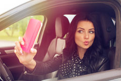 Schöne Brunettefrau, die selfie im Auto tut Stockfoto