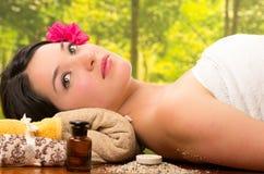 Schöne Brunettefrau, die sich Badekurort im im Freien hinlegt Lizenzfreie Stockfotografie