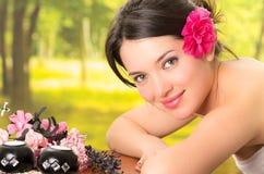Schöne Brunettefrau, die sich Badekurort im im Freien hinlegt Stockfoto