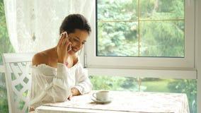 Schöne Brunettefrau, die am Telefon im Restaurant- und Getränkkaffee spricht stock video