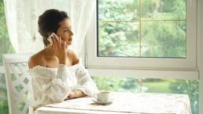 Schöne Brunettefrau, die am Telefon im Restaurant- und Getränkkaffee spricht stock footage