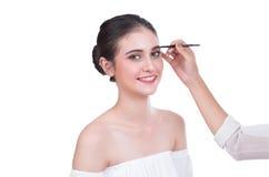 Schöne Brunettefrau malt die Augenbrauen auf weißem Hintergrund Stockbild