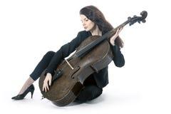 Schöne Brunettefrau mit Cello sitzt auf Boden von Studio agai Stockfoto