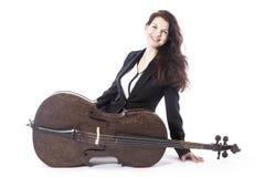 Schöne Brunettefrau mit Cello sitzt auf Boden von Studio agai Lizenzfreies Stockbild