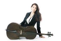 Schöne Brunettefrau mit Cello sitzt auf Boden von Studio agai Stockbilder