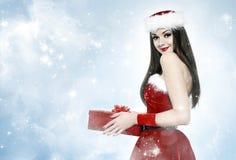 Schöne Brunettefrau mit Geschenk - Weihnachtsporträt lizenzfreie stockbilder