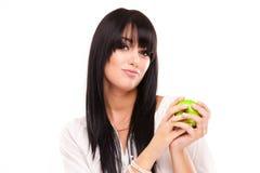 Schöne Brunettefrau mit grünem Apfel auf weißem Hintergrund stockfotografie