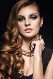 Schöne Brunettefrau mit perfekter Haut, hellem Make-up und Goldschmuck Schönes lächelndes Mädchen Stockfoto